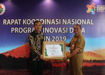 Wakil Bupati Tangerang Mad Romli (kiri) menunjukkan penghargaan PID 2019. (Ist)
