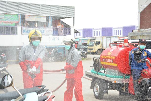 Petugas BPBD Kabupaten menyemprot disinfektan di Pasar Kelapa Dua. (IST)