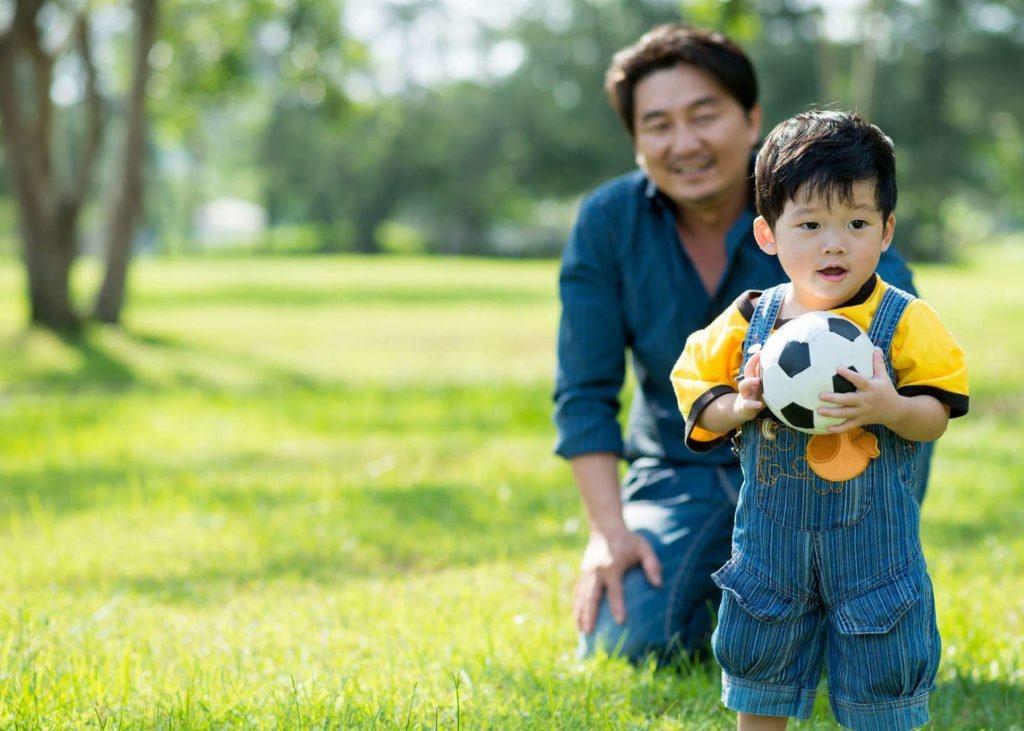 ayah anak laki-laki bermain bola