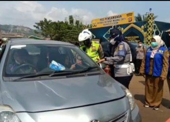 Petugas dari Polda Banten memeriksa kendaraan yang melintas di pos penyekatan. (RAY)