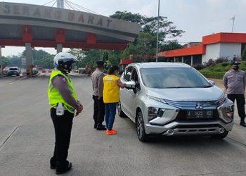 Petugas dari Polda Banten memutarbalikkan kendaraan yang melintas di Gerbang Tol Serang. (IST)