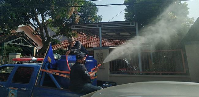 Relawan PPKM Karang Taruna Kota Tangsel menyemprot disinfektan di rumah warga. (IST)